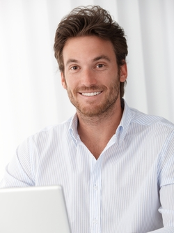 A man with bright, white teeth smiling