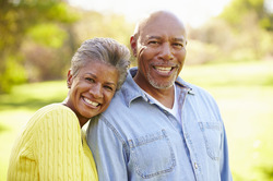 An older couple with healthy and complete smiles