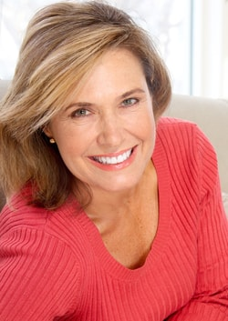 A woman with side swept brown hair and a coral sweater smiles warmly toward the camera