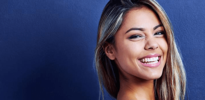 Smiling young woman in front of blue background