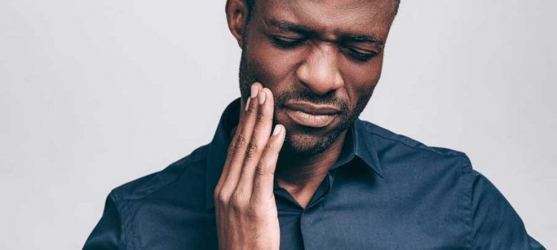 man with facial scruff and blue button up in tooth pain touching side of face