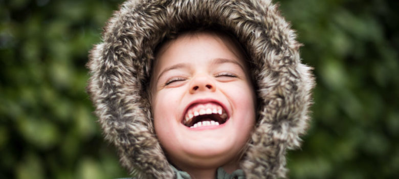 Young child with a loose tooth laughs and smiles while wearing a green hooded jacket lined with faux fur